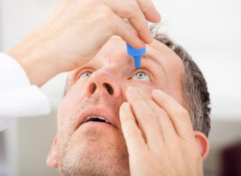 Middle aged man putting eye drops into his eyes, and facing upwards.