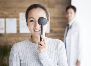 Woman covering eye during eye exam
