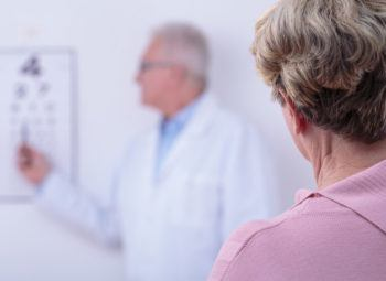 Woman reading from a Snellen eye chart during eye exam.