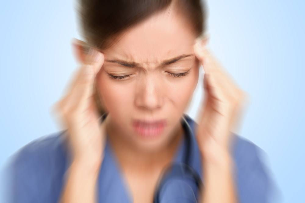 Woman suffering from migraine with aura.