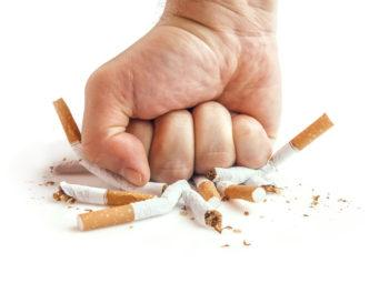 Fist crushing multiple cigarettes.