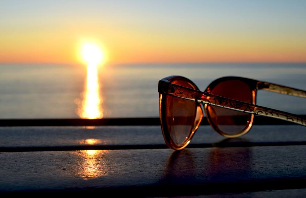 A pair of sunglasses sitting on table at the ocean shore during sunset.