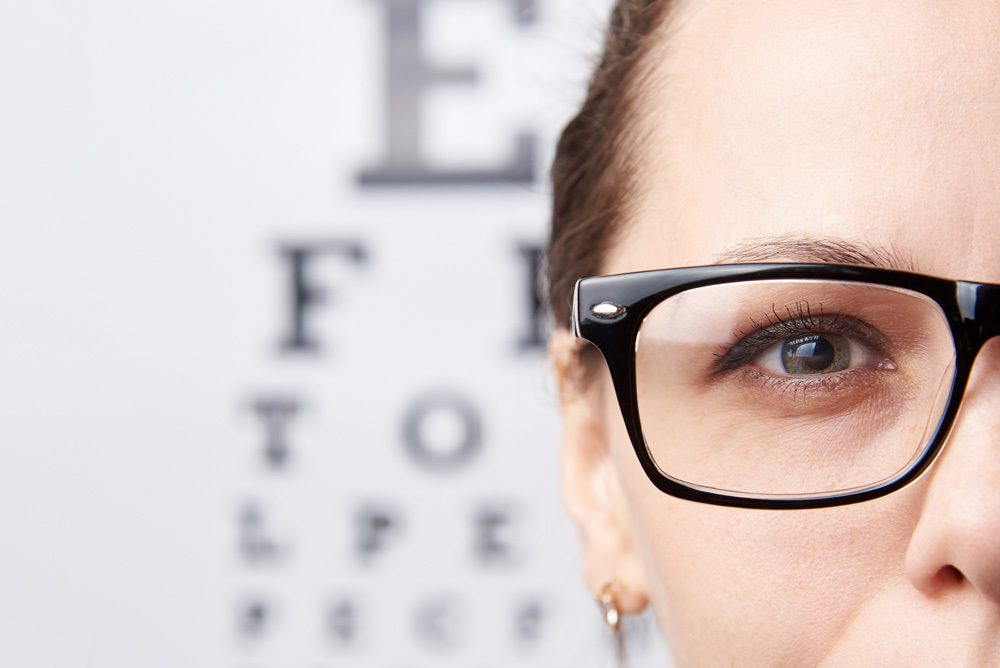 Woman with glasses standing in front of Snellen eye chart.
