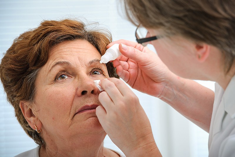 woman tilting her head back and receiving eye drops from eye doctor