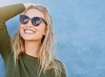 blonde woman looking up and brushing back hair with sunglasses on