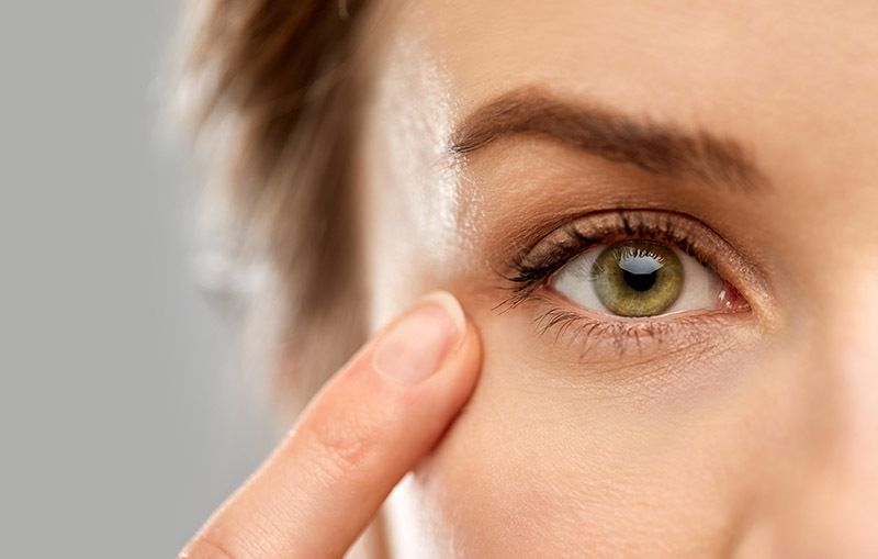 close up of a women's face pointing a finger to her green eye