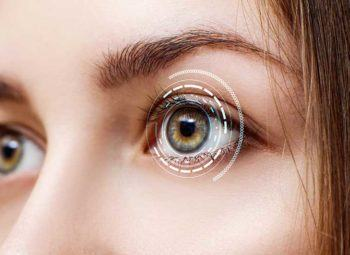 close-up of young women eyes with high tech scan imaging