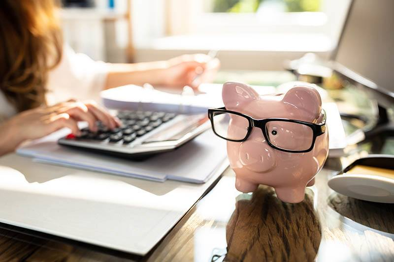person Calculating Bill In Front Of Pink Piggy Bank with glasses on Over Desk