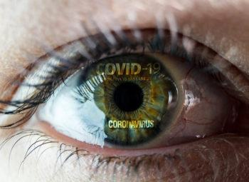 close up of eye with the worlds covid-19 and coronavirus reflected in it