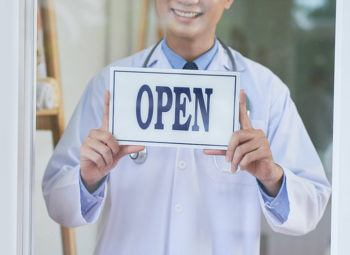 Doctor with Open sign welcoming patients into the clinic