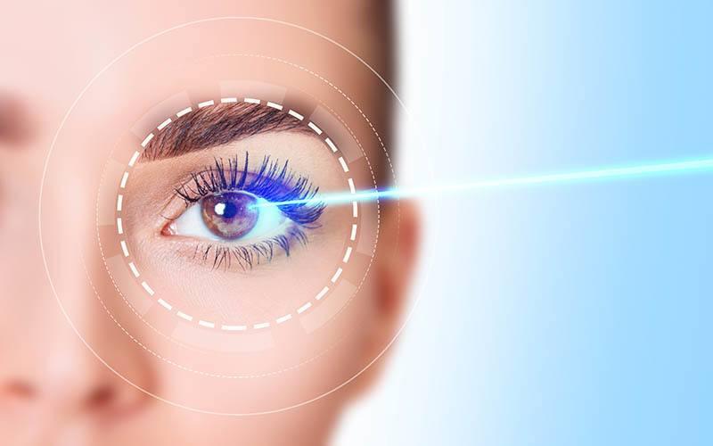Beautiful female eye with blue laser ray. Vision correction surgery on female eye.