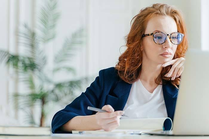 women in eyeglasses on laptop researching LASIK surgeons