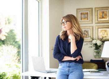 Women standing in home office wearing eyeglasses and looking thoughtful