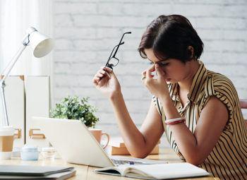 women with eyeglasses sitting at work desk rubbing her eyes