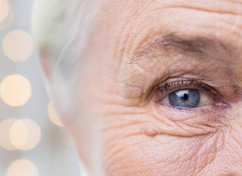 half of elderly womans face with speckles of light behind her head