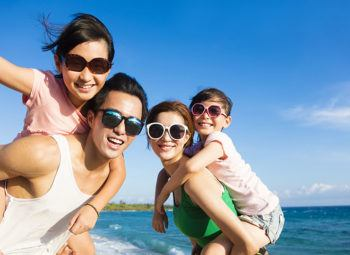 Happy Family of four wearing UV protective sunglasses and Having Fun at the Beach